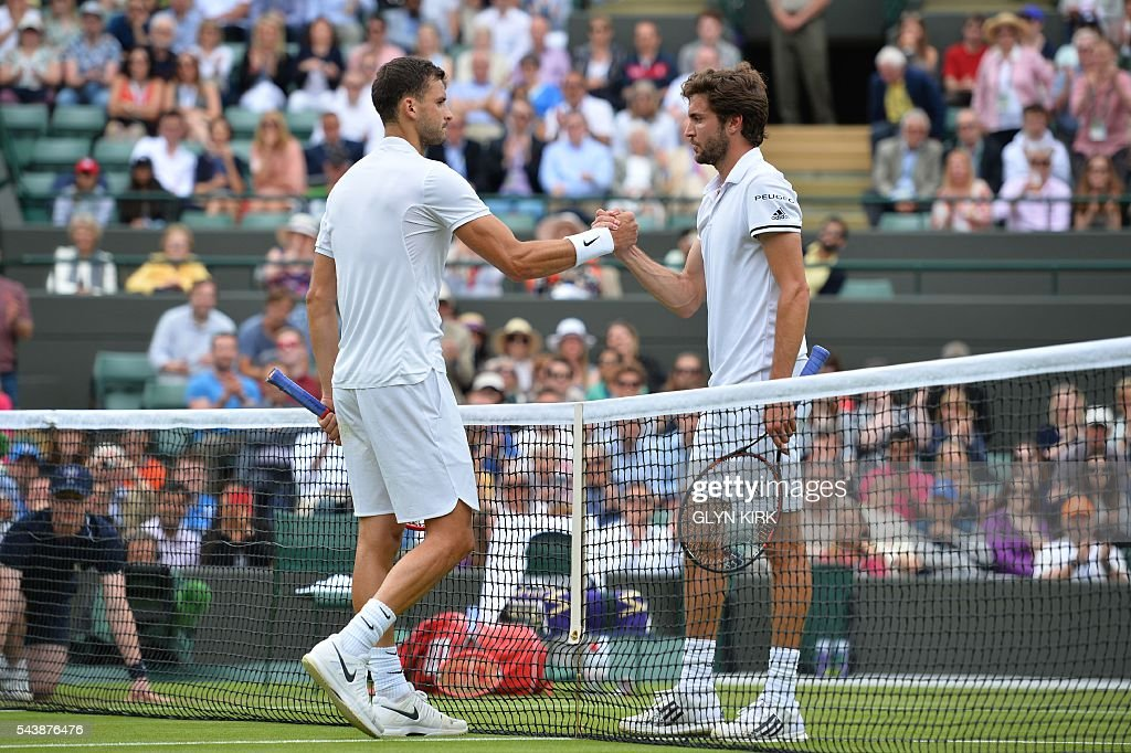 Bulgaria's Grigor Dimitrov (L) shakes hands with France's Gilles Simon (R) after Dimitrov won their men's singles second round match on the fourth day of the 2016 Wimbledon Championships at The All England Lawn Tennis Club in Wimbledon, southwest London, on June 30, 2016. / AFP / GLYN