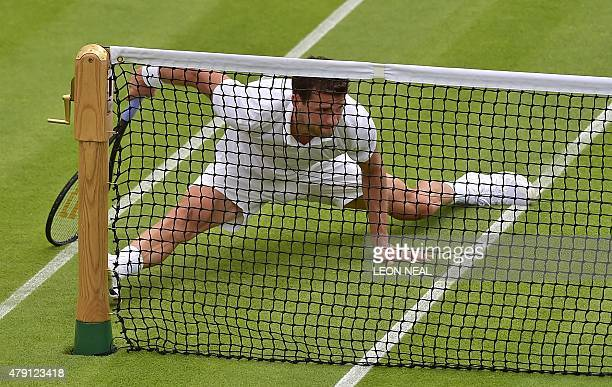 Bulgaria's Grigor Dimitrov slips on the grass after jumping to return to US player Steve Johnson during their men's singles second round match on day...