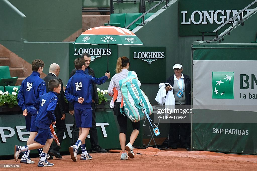 Bulgaria's Tsvetana Pironkova leaves the court as play is interrupted due to rain during her women's fourth round match against Poland's Agnieszka Radwanska at the Roland Garros 2016 French Tennis Open in Paris on May 31, 2016. / AFP / PHILIPPE