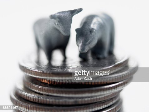 Bull and bear figurines on top of stack of quarters : Stock Photo