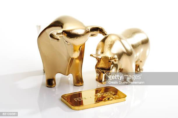 Bull and bear figurines and gold bar, close-up