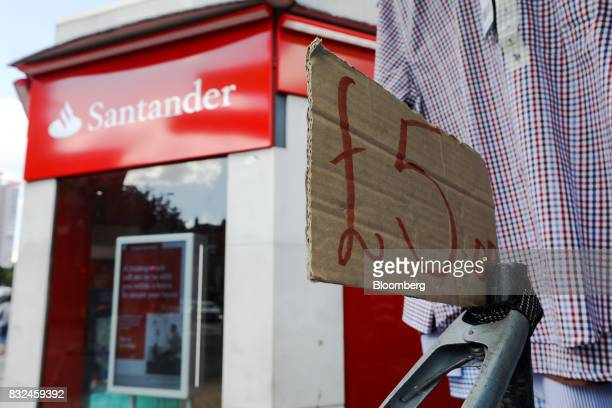A bull dog clip holds a sign advertising a pound sterling price near a clothing rail at a market stall next to a bank branch of Banco Santander SA in...