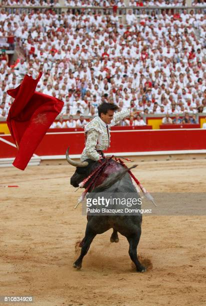 A bull from Jose Escolar Gil's fighting bulls tosses Spanish bullfighter Gonzalo Caballero during a bullfight on the third day of the San Fermin...