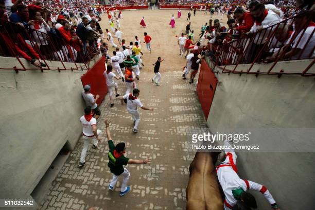 A bull from Puerto de San Lorenzo's fighting bulls tosses a reveller entering the bullring during the fourth day of the San Fermin Running of the...