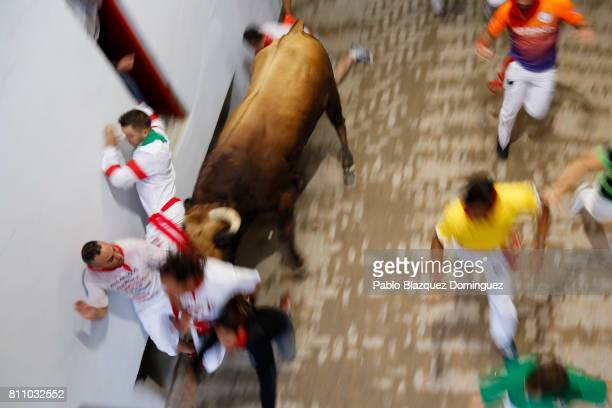 A bull from Puerto de San Lorenzo's fighting bulls tosses to revellers entering the bullring during the fourth day of the San Fermin Running of the...