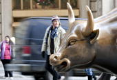 A bull statue stands in the Financial District near the New York Stock Exchange in New York US on Friday Dec 18 2009 US stocks rose trimming a weekly...