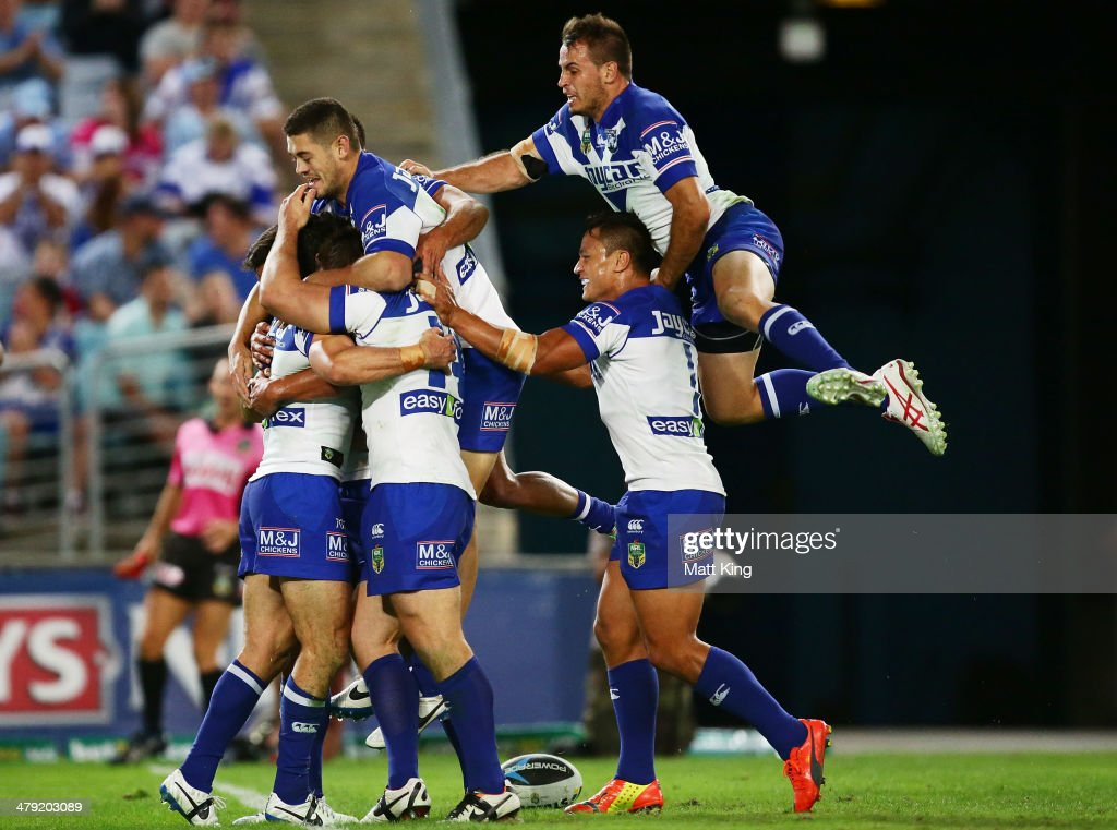 Bulldogs players celebrate the try to Michael Ennis as Josh Reynolds jumps over the top during the round two NRL match between the...