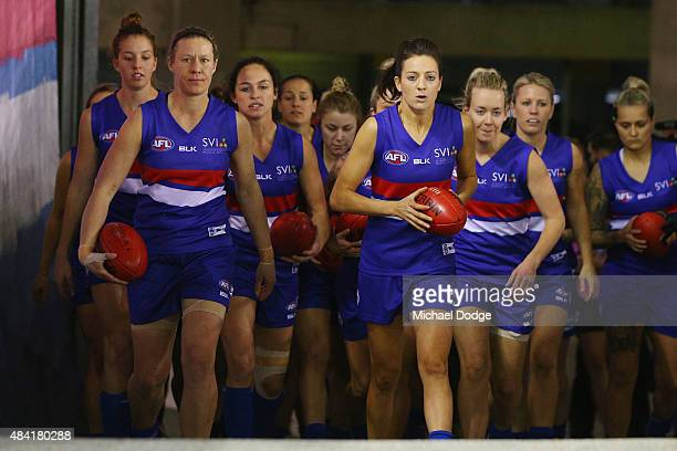 Bulldogs players walk to their banner during a Women's AFL exhibition match between Western Bulldogs and Melbourne at Etihad Stadium on August 16...