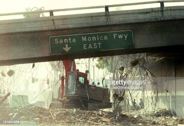 A bulldozer begins to tear down a section of the Santa Monica Freeway 19 January 1994 that collapsed during the Northridge earthquake Commuters were...