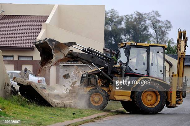 A bulldozer breaks down the garden wall of a house that has been built illegally on November 9 2012 in Lenesia south west of Johannesburg Earlier...