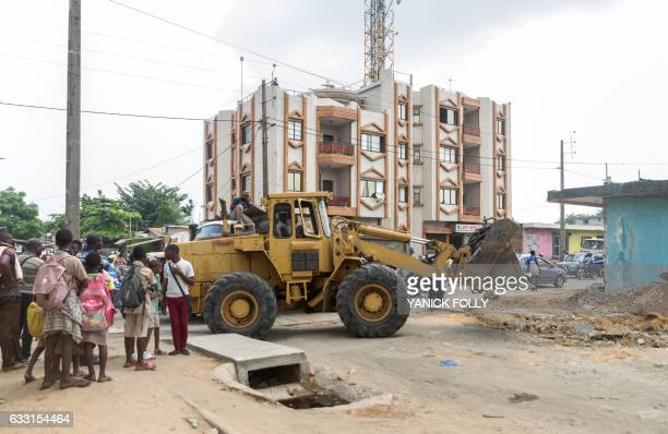 A bulldozer clears rubble from a street after the demolition of a structure built on state property in the capital Cotonou in Benin on January 26...