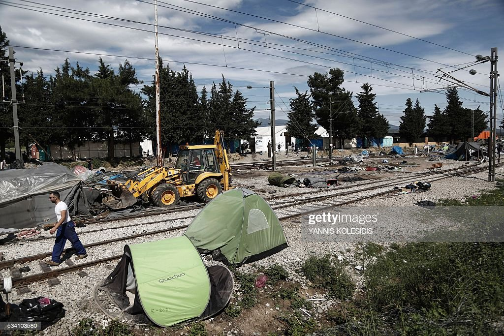 A bulldozer clears the debris at the site of the makeshift camp housing refugees and migrants in Idomeni, close to the Macedinian border on May 25, 2016. For a second day Greek police restarted an operation to move migrants out of Idomeni, the squalid tent city where thousands fleeing war and poverty have lived for months. The migrants and refugees are bring bussed to newly opened camps near Greece's second city Thessaloniki, about 80 kilometres (50 miles) to the south. / AFP / POOL / Yannis KOLESIDIS