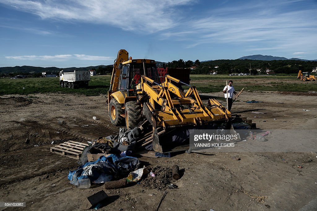 A bulldozer clears the debris at the site of the makeshift camp in Idomeni on May 25, 2016. Greek police restarted an operation to move migrants out of Idomeni, the squalid tent city where thousands fleeing war and poverty have lived for months. The migrants and refugees were bussed to newly opened camps near Greece's second city Thessaloniki, about 80 kilometres (50 miles) to the south. / AFP / POOL / Yannis KOLESIDIS