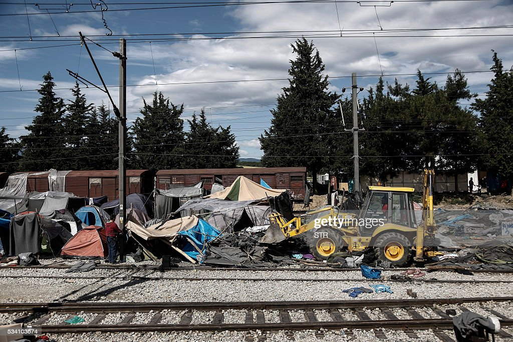 A bulldozer clears the debris at the site of the makeshift refugee and migrant camp in Idomeni close to the Greek-Macedonian border on May 25, 2016. Greek police restarted an operation to move migrants out of Idomeni, the squalid tent city where thousands fleeing war and poverty have lived for months. The migrants and refugees were bussed to newly opened camps near Greece's second city Thessaloniki, about 80 kilometres (50 miles) to the south. / AFP / POOL / STR
