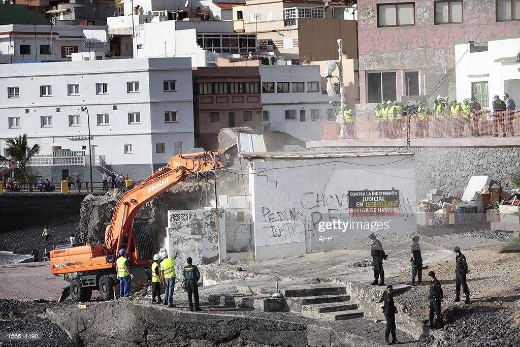A bulldozer demolishes a house after neighbors where evicted by Spanish Guardia Civil members in the fishing village of Chovito on the Spanish Canary Island of Tenerife, on November 16, 2012. Six neighbors have been on hunger strike to protest a court decision requiring the demolition of their houses according to the Spanish Coastal Law. AFP PHOTO/DESIREE MARTIN
