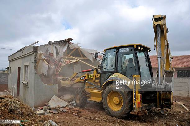A bulldozer demolishes a house on November 9 2012 that had been built illegally in Lenesia south west of Johannesburg Earlier today protesters have...