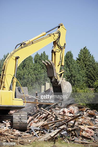 A bulldozer demolishing something wooden on clear blue day.