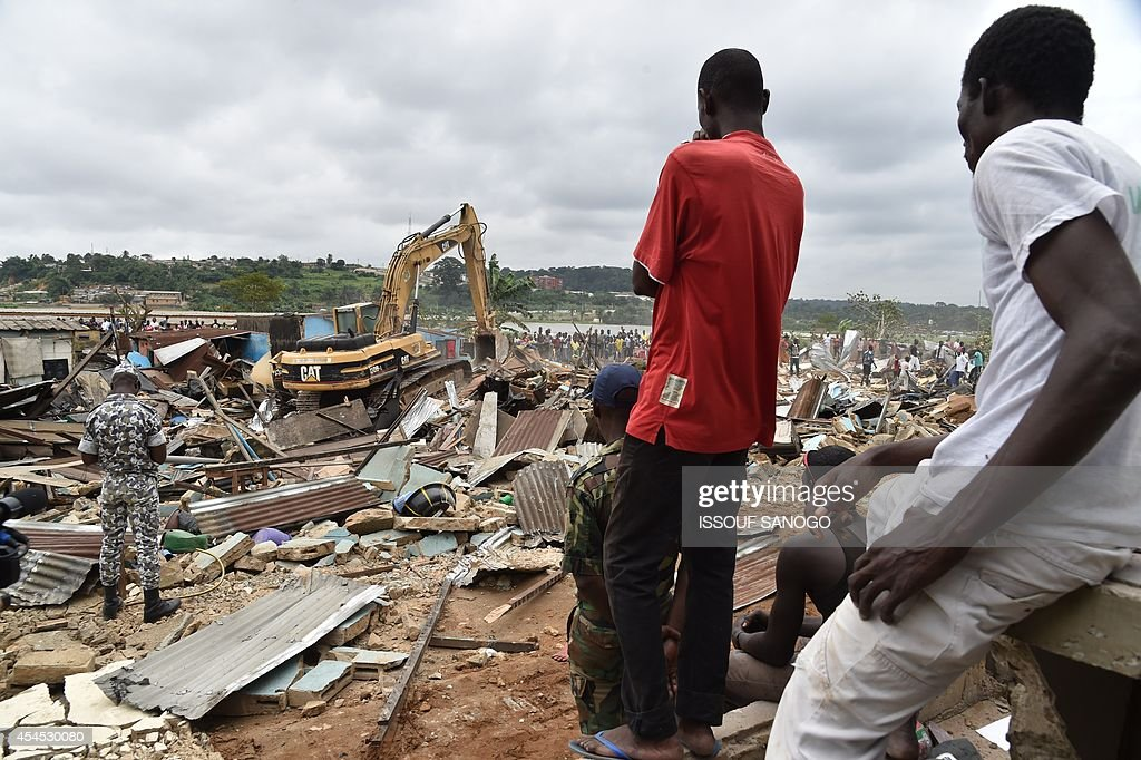 A bulldozer destroys unstable habitations built on hill slopes deemed as landslide prone, in Attecoube commune, a poor sector of the Ivorian capital Abidjan, on September 2, 2014. About 39 people have died because of landslides since the beginning of the rainy season on June in Abidjan. 350 000 people live in Attecoube, most of them in terrible conditions and on unstable ground, making them particularly vulnerable to floods and landslides. AFP PHOTO / ISSOUF SANOGO