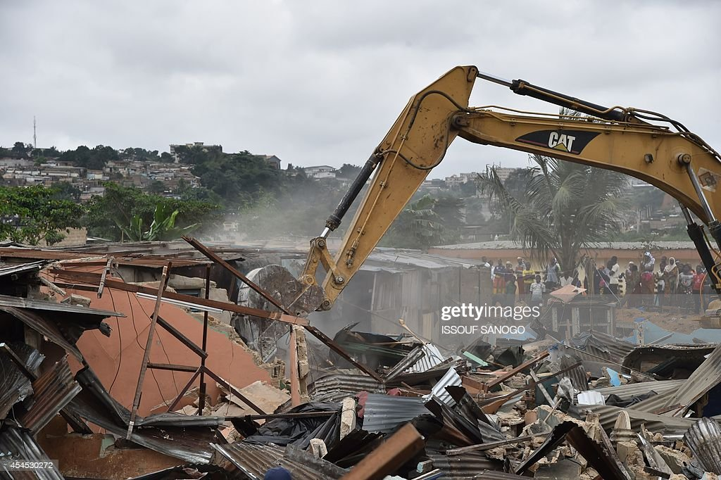 A bulldozer destroys unstable habitations built on hill slopes deemed as landslide prone, in Attecoube commune, a poor sector of the Ivorian capital Abidjan, on September 2, 2014. About 39 people have died because of landslides since the beginning of the rainy season on June in Abidjan. 350 000 people live in Attecoube, most of them in terrible conditions and on unstable ground, making them particularly vulnerable to floods and landslides.
