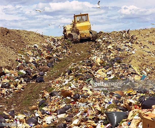 A bulldozer driving up a hill of garbage