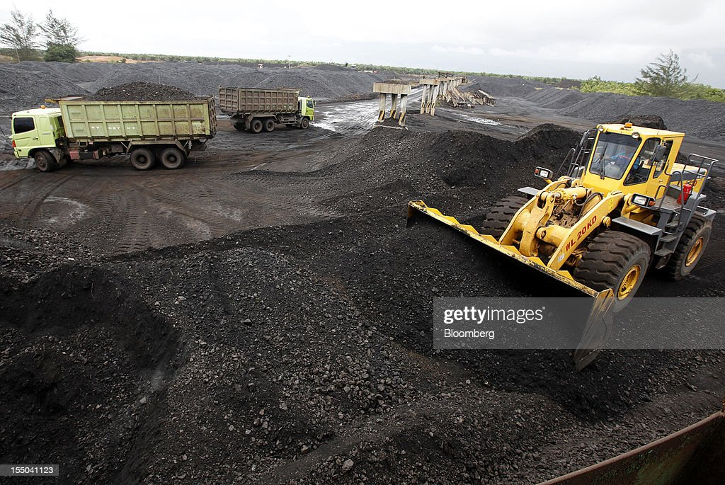 A bulldozer forms a stockpile of coal at the PT Exploitasi Energi Indonesia operations in Asam-Asam, South Kalimantan, Indonesia, on Monday Oct. 29, 2012. Indonesia, the world's largest exporter of coal for electricity generation, will reduce the amount of the fuel that producers must sell to buyers inside the country for next year by 9.4 percent. Photographer: Dadang Tri/Bloomberg via Getty Images