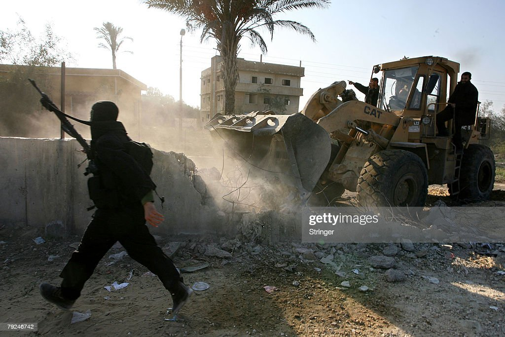 A bulldozer is used to destroy a section of the border wall between the Gaza Strip and Egypt January 25, 2008 in the town of Rafah, in the southern Gaza Strip. Militants open up new breaches on the border with Egypt after Egyptian security forces tried to retake control of the border and stop Palestinians from entering Egypt.