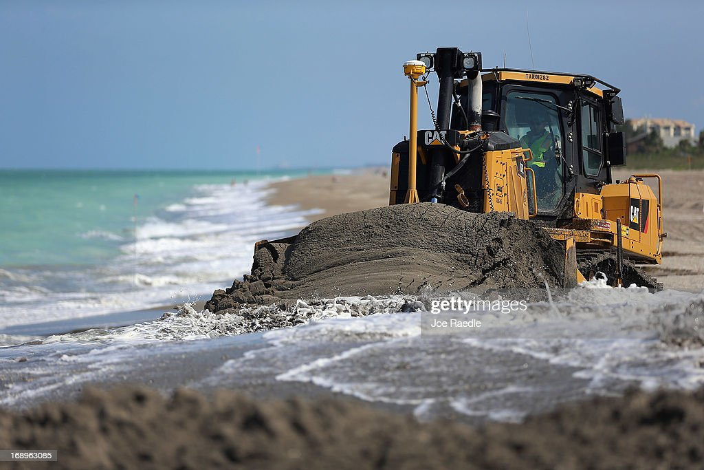 A bulldozer is used to push sand from a discharge pipe into place during a federally funded shore protection project by Great Lakes Dredge and Dock...