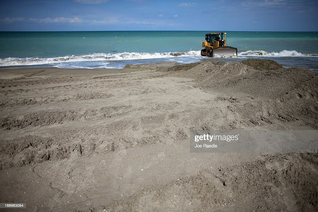 A bulldozer is used to push sand from a discharge pipe into place during a federally funded shore protection project by Great Lakes Dredge and Dock on May 17, 2013 in Fort Pierce, Florida. As cities along the East Coast prepare for the start of the hurricane season, officials say the area encompasing Fort Pierce beach has been in dire need of repair since Hurricane Sandy last year made worse an area already suffering significantly from erosion. Some experts say shore restoration projects can help reduce the physical and economic damage from waves, storm surge, and the resulting coastal flooding in a hurricane.