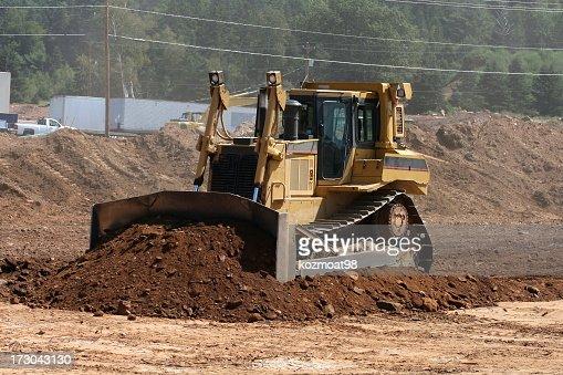 Bulldozer moving soil in construction area