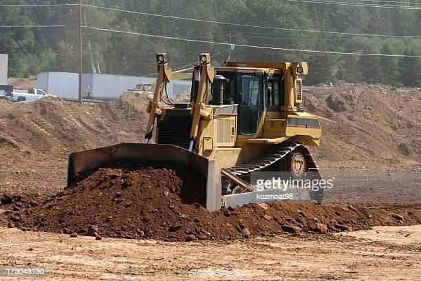 Bulldozer moving soil in construction area
