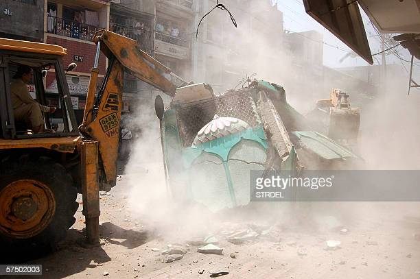 A bulldozer of the Vadodara Municipal Corporation demolishes a Muslim shrine in the western city of Vadodara 01 May 2006 Two people were killed when...