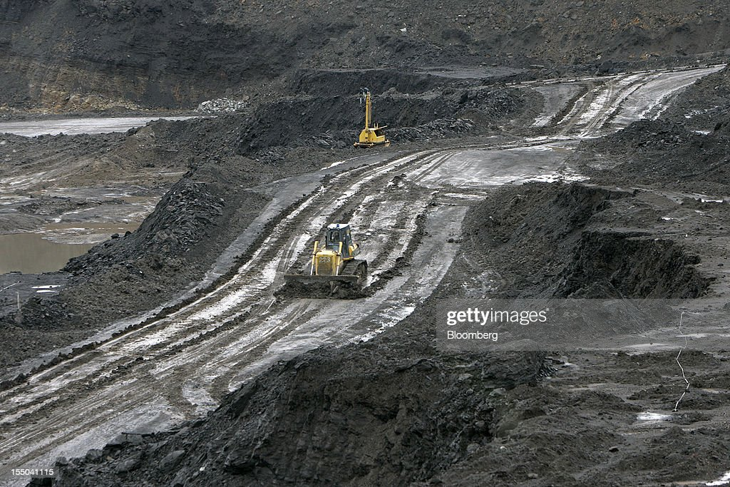 A bulldozer operates in the open pit coal mine at the PT Exploitasi Energi Indonesia operations in Asam-Asam, South Kalimantan, Indonesia, on Monday Oct. 29, 2012. Indonesia, the world's largest exporter of coal for electricity generation, will reduce the amount of the fuel that producers must sell to buyers inside the country for next year by 9.4 percent. Photographer: Dadang Tri/Bloomberg via Getty Images