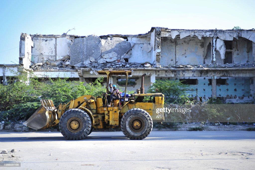 A bulldozer passes in front of a destroyed building in the Somali capital Mogadishu on November 18, 2012. While much of the city has been damaged by two decades of civil war, a newfound peace in the city has meant that construction is now on the rise again. AFP PHOTO / AU-UN IST / TOBIN JONES --- RESTRICTED TO EDITORIAL USE - MANDATORY CREDIT 'AFP PHOTO / AU-UN IST / TOBIN JONES' - NO