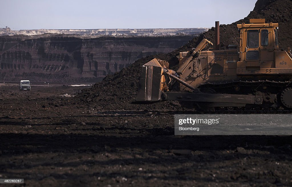 A bulldozer prepares to shift loose earth in the pit during lignite, also known as brown coal, digging operations at the open pit mine operated by PGE Elektrownia Belchatow SA near Belchatow, Poland, on Wednesday, April 2, 2014. Polish power prices are set to stay above German contracts through 2015, reversing a historic discount, as the cost of keeping plants open in the eastern European nation is factored in, according to Vattenfall AB. Photographer: Bartek Sadowski/Bloomberg via Getty Images