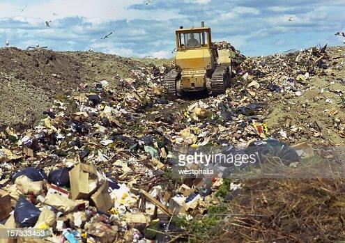 Bulldozer pushing trash in landfill