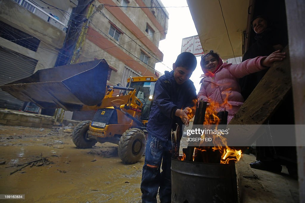 A bulldozer, removing garbage, mud and water from flooded streets, drives past children warming their hands on an open fire in Beirut's southern impoverished suburb of Hayy al-Sellum on January 9, 2013 as heavy rains and high speed winds hit Lebanon. A met office official at Beirut airport said the storm would continue and that lower temperatures would result in snowfall in the mountains as low as 300 metres.