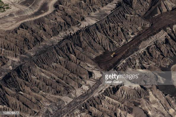A bulldozer stands among patterns of soil called overburden redeposited in successive layers as part of strip mining in the Jaenschwalde openpit...