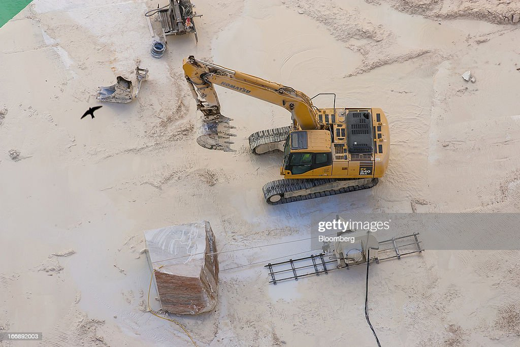 A bulldozer stands next to a block of raw marble being cut inside a quarry pit operated by Bloco B in Pardais, Vila Vicosa, Portugal, on Wednesday, April 17, 2013. Portugal is posting its first trade surplus in at least six decades, which may help vindicate a strategy of front-loading austerity to deliver economic reform. Photographer: Mario Proenca/Bloomberg via Getty Images