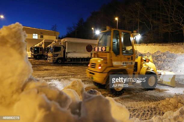 A bulldozer sweeps snow from the road as trailers are stuck at a parking in Karuizawa in Nagano prefecture central Japan on February 17 2014 A severe...