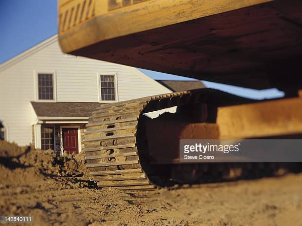 A bulldozer with a yellow house in the background