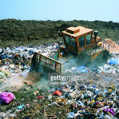 Bulldozer working on landfill site,UK : Stock Photo