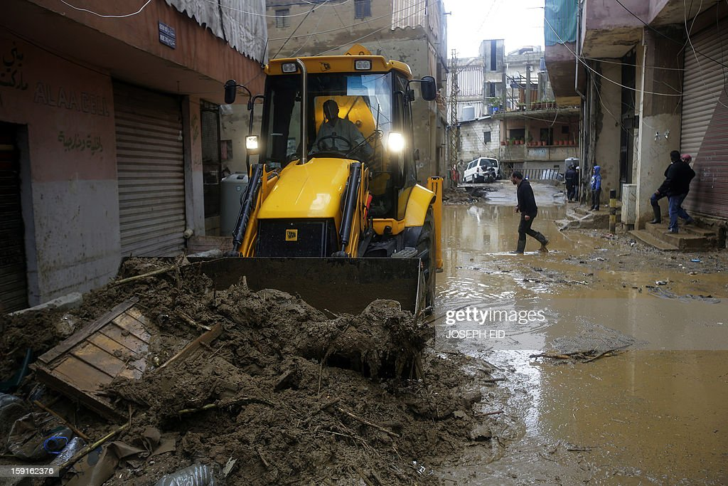 A bulldozer works on removing garbage, mud and water from the flooded streets in Beirut's southern suburb of Hayy al-Sellum on January 9, 2013 as heavy rains and high speed winds hit Lebanon. A met office official at Beirut airport said the storm would continue and that lower temperatures would result in snowfall in the mountains as low as 300 metres.