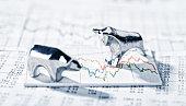 Bulle und Bär stehen auf einer Grafik mit Börsenkursen.