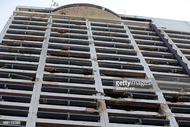 Bullet and rocket marks cover the walls of the abandoned building of the Holiday Inn hotel in the Lebanese capital Beirut on April 11 2014 A symbol...