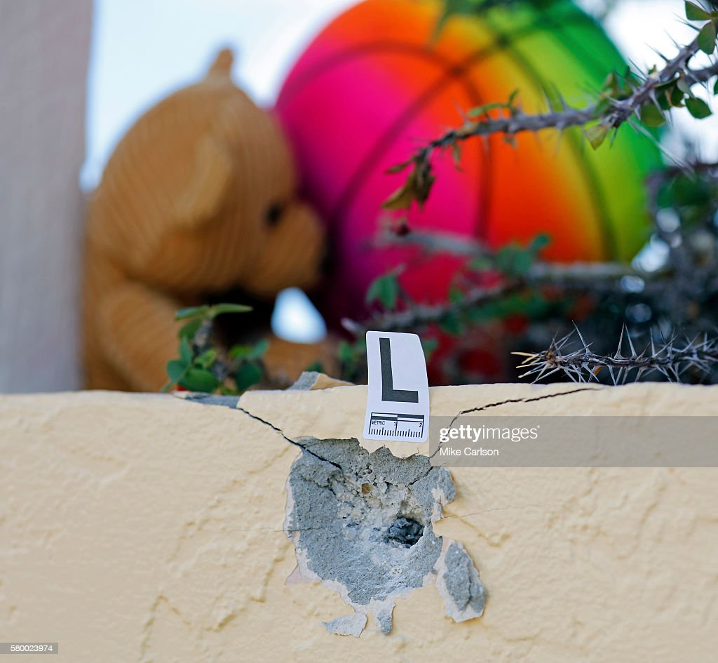 A bullet hole is marked by police as a small memorial grows outside of Club Blu where two people were killed and at least 15 were wounded on July 25...