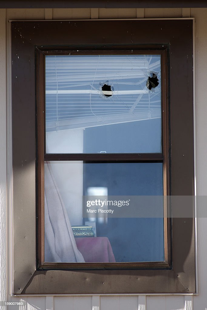 Bullet holes are seen in an upper window of a town home where four people were killed Saturday morning including the gunman who held police at bay for several hours at the complex January 5, 2013 in Aurora, Colorado. Aurora SWAT team members shot a gunman after he went to a second-floor window and fired at police. The gunman also allegedly fatally shot two men and a woman that he had taken hostage. One woman managed to escape from an upstairs back window, ran from the home and called police just before 3 a.m., said Cassidee Carlson, Aurora police spokeswoman.