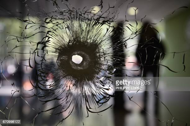 A bullet impact is pictured on a window in the entrance hall of a building on the Champs Elysees avenue in Paris on April 21 2017 a day after a...