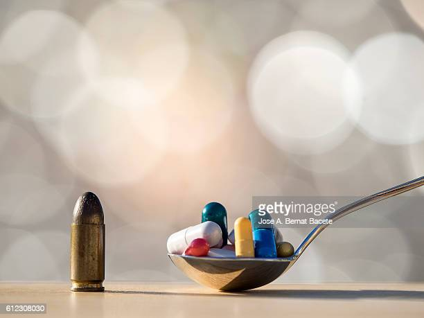 Bullet of a pistol and spoon with many medicines, difficult decisions
