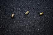 Cases of bullets lying on the floor of asphalt