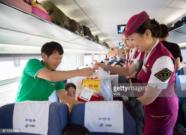 A bullet train attendant hands takeout food to passengers who order food online on July 17 2017 in Changsha Hunan Province of China Passengers who...